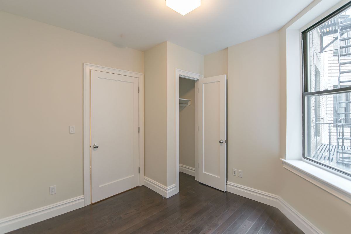 A bedroom with beige walls, base moldings, a small closet, and a window.