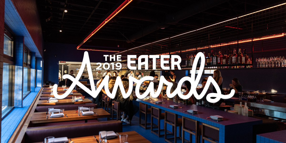 """A blue tiled room with wood tables at Magnet with """"The 2019 Eater Awards"""" written in white across the front of the image."""