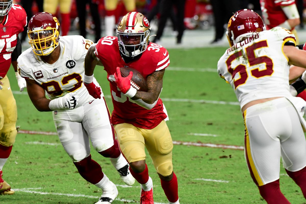 San Francisco 49ers running back Jeff Wilson runs the ball as Washington Football Team defensive tackle Jonathan Allen defends during the first half at State Farm Stadium.
