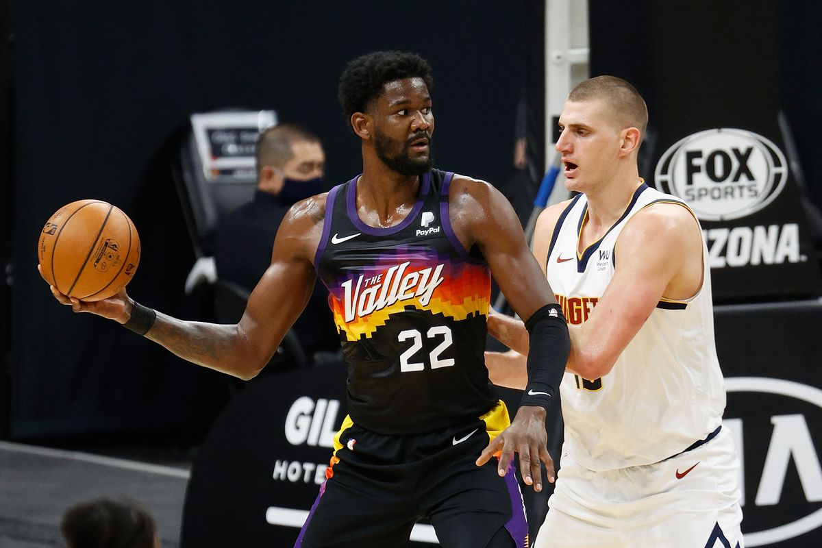 Deandre Ayton #22 of the Phoenix Suns looks to pass around Nikola Jokic #15 of the Denver Nuggets during the NBA game at Phoenix Suns Arena on January 23, 2021 in Phoenix, Arizona.