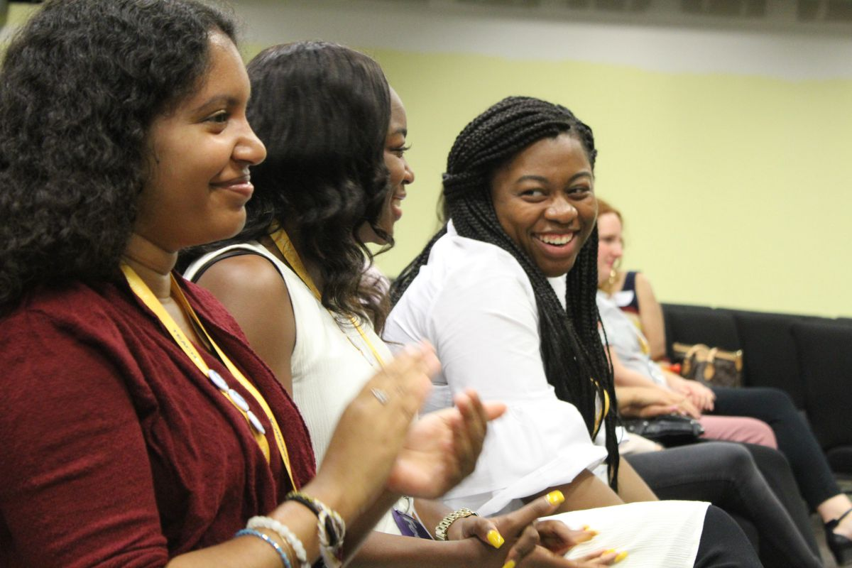 Incoming corps members clap for students during panel discussion.