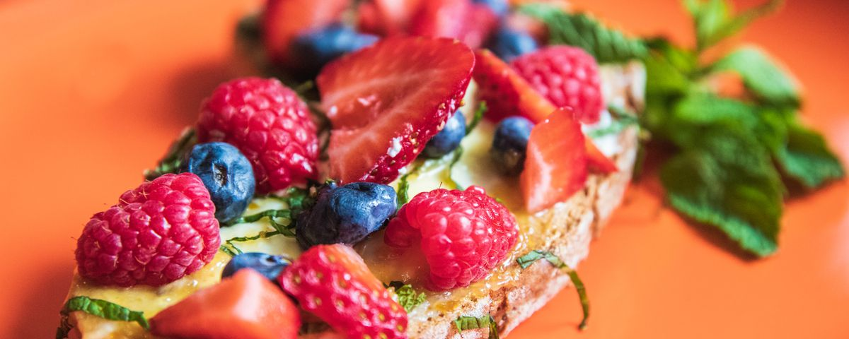 A scrumptious piece of toast loaded up with fruit.,