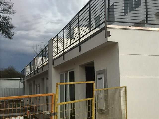 gray condo building under construction, two stories, deck with metal railing