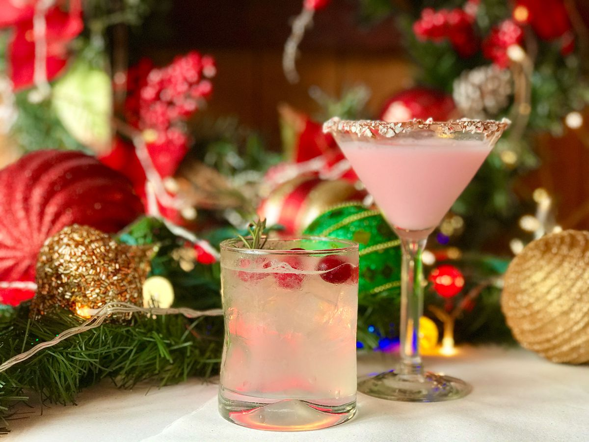 Pink holiday cocktails on a white table with lots of Christmas decorations.
