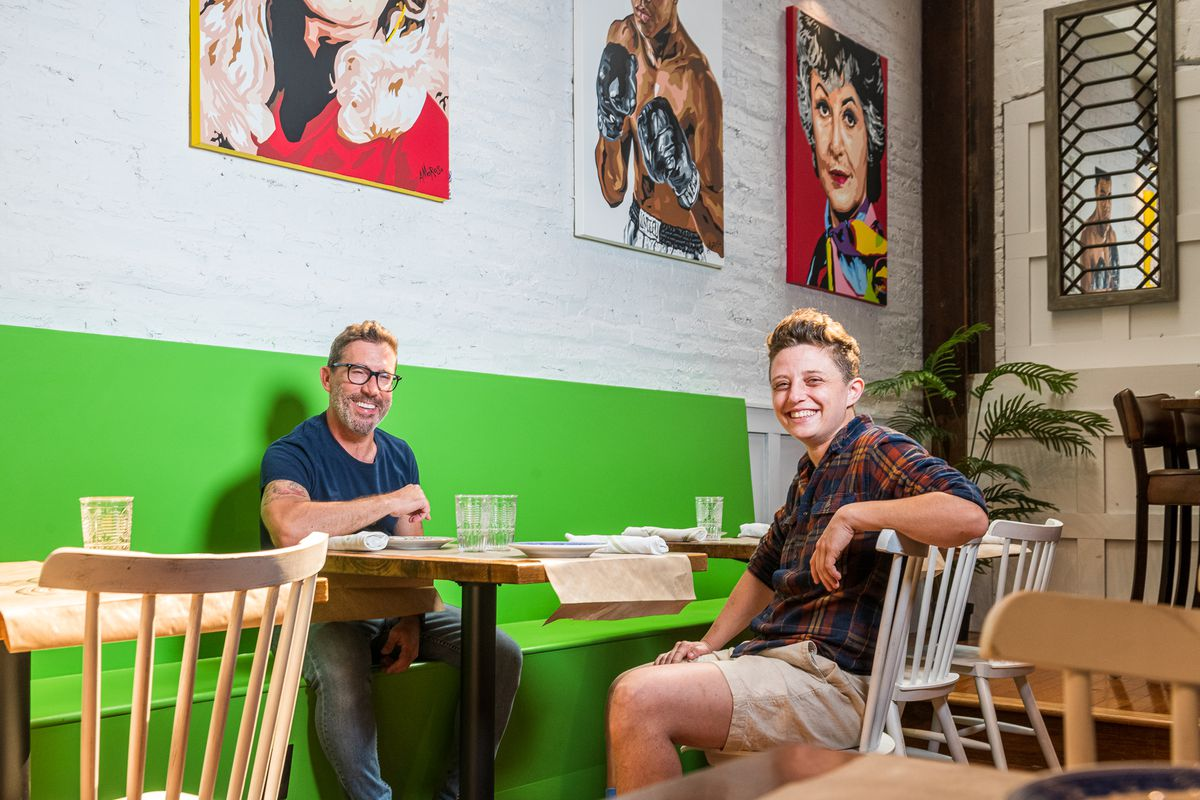 Crazy Aunt Helen's owner Shane Mayson and chef Mykie Moll pose for a picture while seated at a dining room table that adjoins a bright green bench.