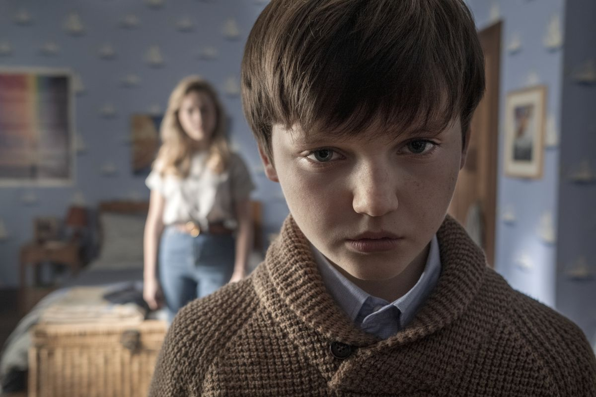 A creepy kid stands in close-up in a haunted house