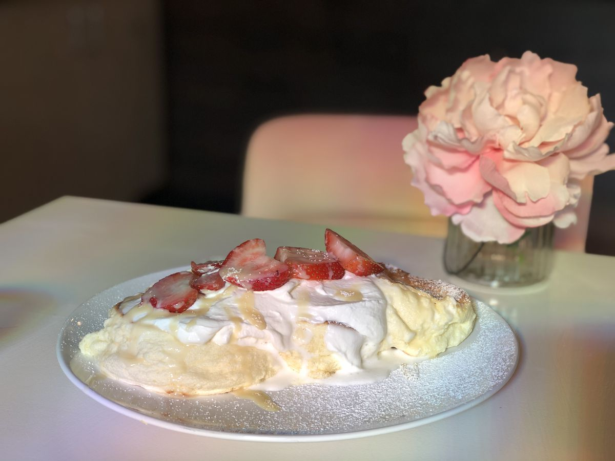 Thick, soft round pancakes topped with whipped cream and strawberries