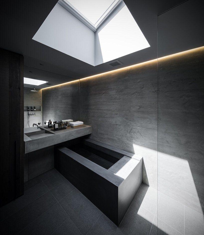 All-concrete bathroom with an angular concrete bath tub and skylight overhead.