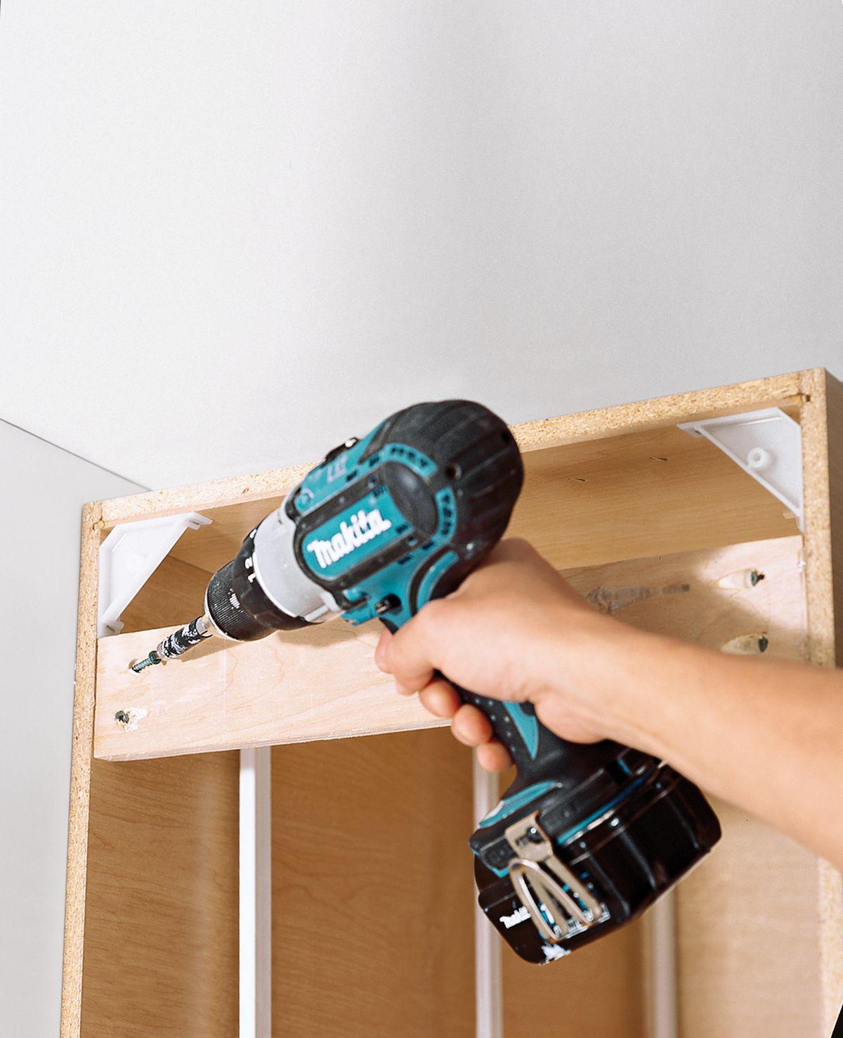 Man Prepares Cabinets Of DIY Butcher Block Countertop