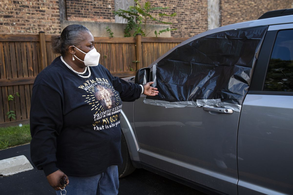 Anna Johnson shows how her van's windows shot out near her home in the 600 block of West 61st Street. A 4-year-old girl was wounded on the Englewood block Tuesday afternoon.