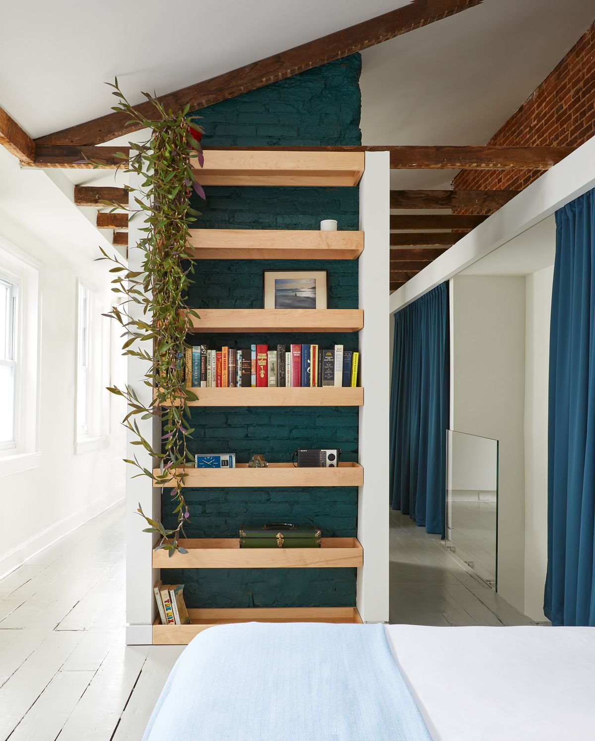 Floor to ceiling wooden shelves are full of books and objects. The shelves are attached to dark blue painted exposed brick. There are wooden beams on the ceiling. The floor is painted white hardwood. The walls are white.