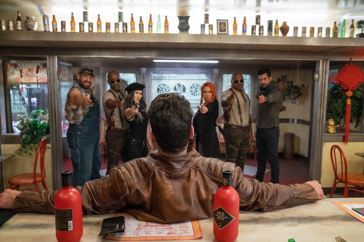 Six assassins prepare to gun down Roy Pulver, seated at a bar.
