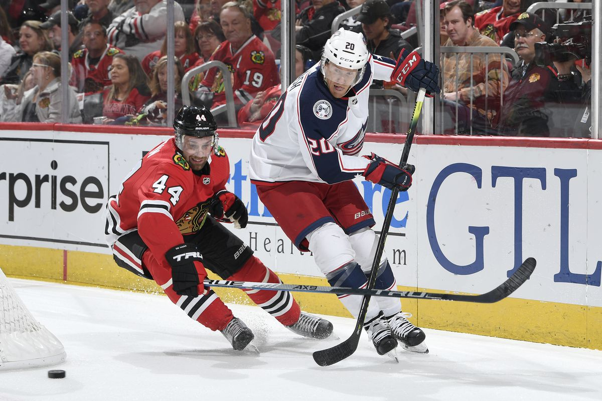 Calvin de Haan of the Chicago Blackhawks and Riley Nash of the Columbus Blue Jackets chase the puck in the second period at the United Center on October 18, 2019 in Chicago, Illinois.