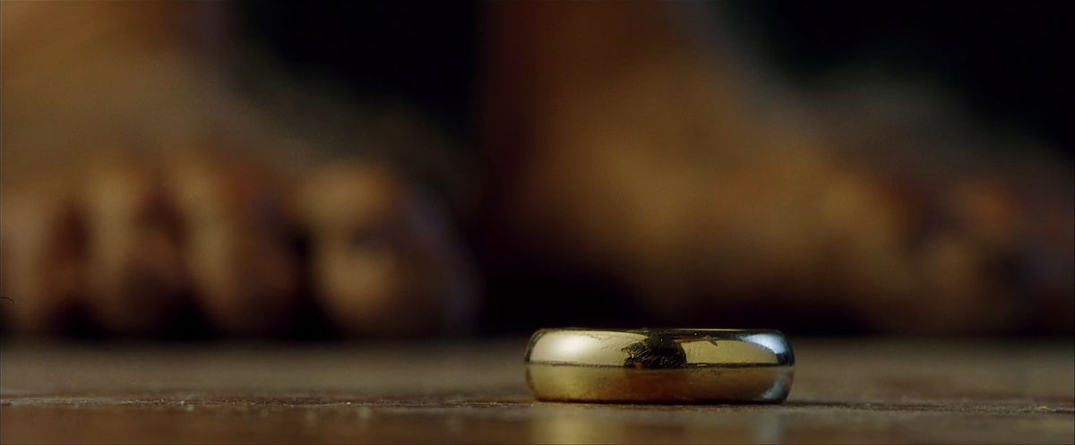 The One Ring lies on the floor of Bag End, Bilbo's toes out of focus in the background in The Fellowship of the Ring.
