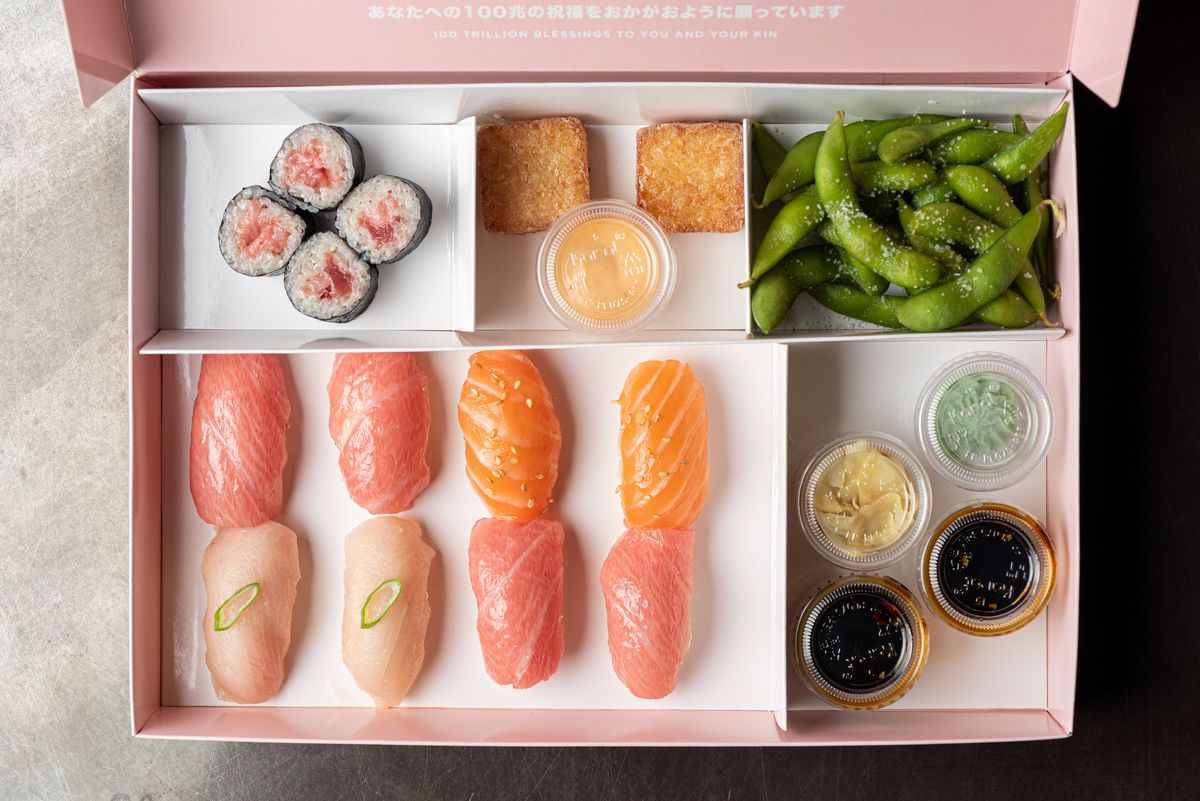 An overhead look at sushi inside of a bright pink box.