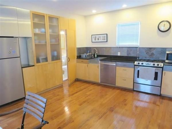 An open kitchen with appliances and a set of floor-to-ceiling cabinets.