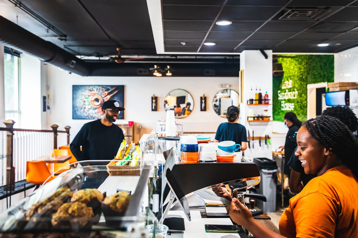A busy cafe space with smiling employees