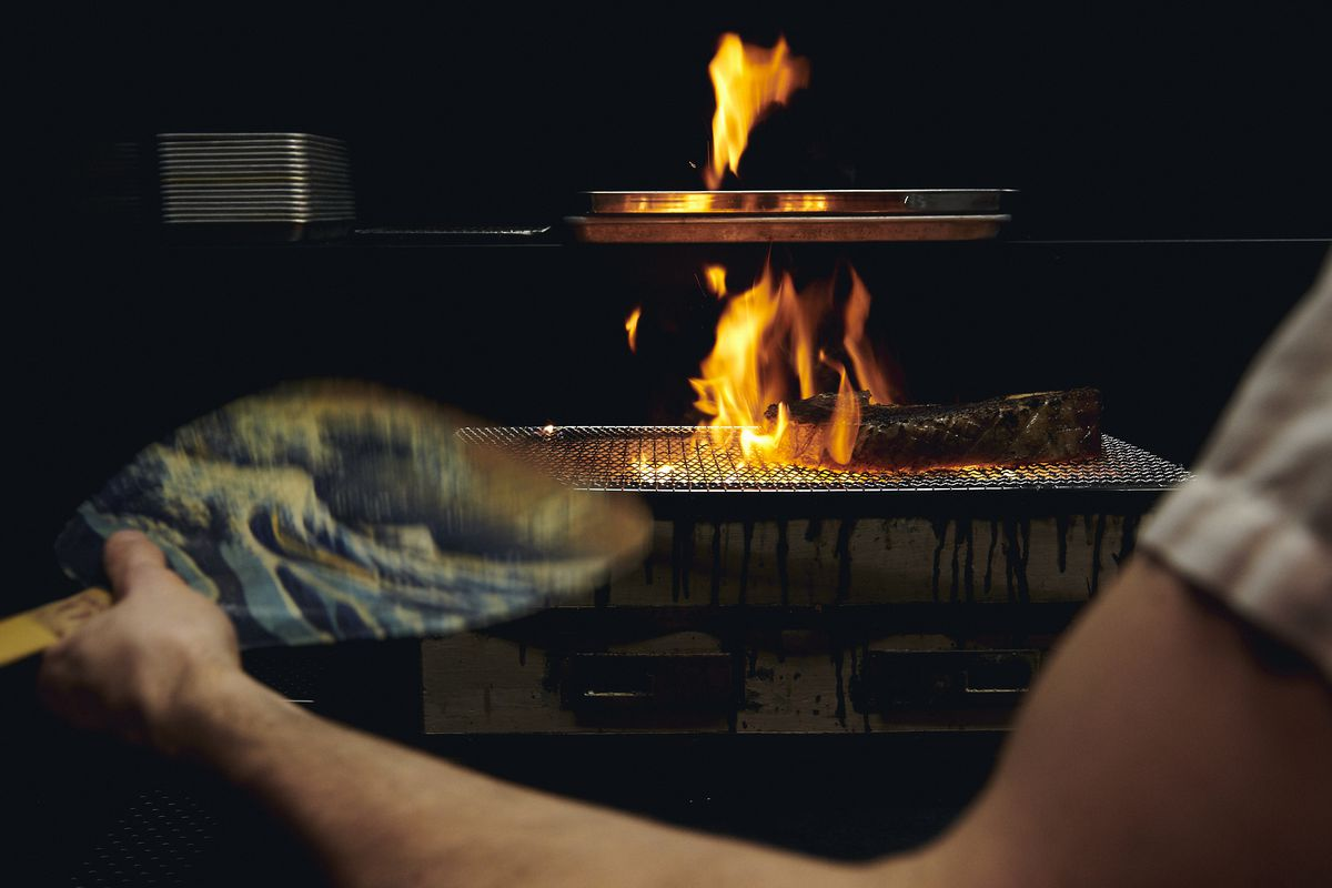 A chef fans the flames over the grill at Momofuku Ko's Bar