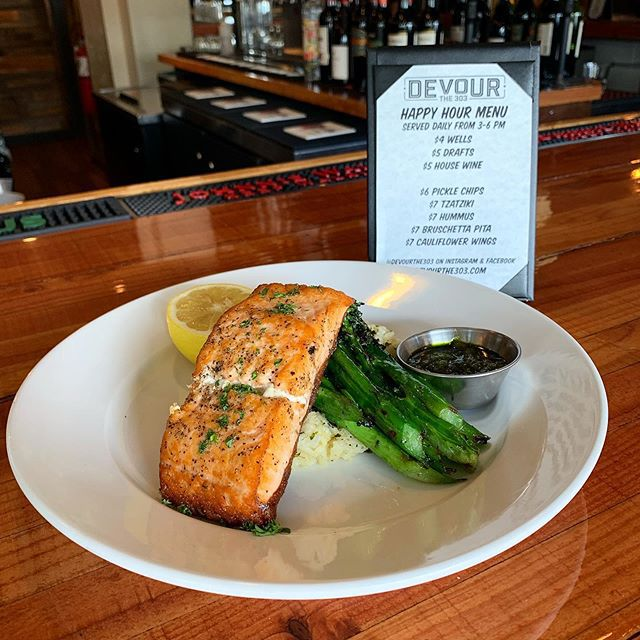 A picture of a piece of grilled salmon and pieces of asparagus with lemon and sauce on a plate at Devour the 303