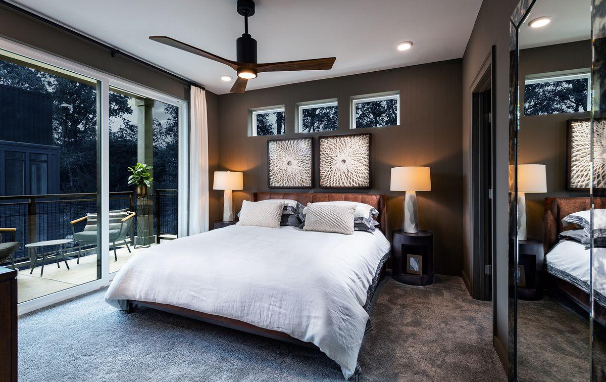 Bedroom with brown walls, king bed, nightstands with lamps, and floor-to-ceiling doors overlooking the patio.