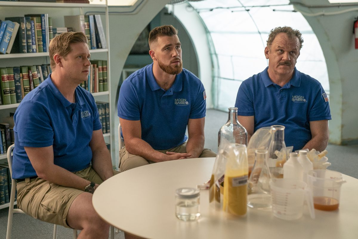 Tim Heidecker and John C. Reilly sit with NFL player Travis Kelce (as himself) in Moonbase 8