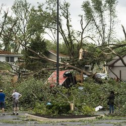 Residents look at the damage to St Scholastica Catholic Church, at 7800 Janes Ave. in Woodridge, and surrounding buildings after a tornado ripped through the western suburbs overnight, Monday morning, June 21, 2021.