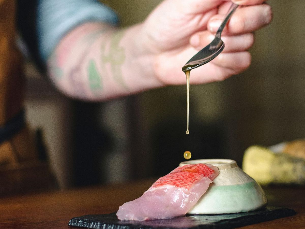 Oil being dropped from a spoon onto a piece of pink sushi with scales on, resting on a bowl