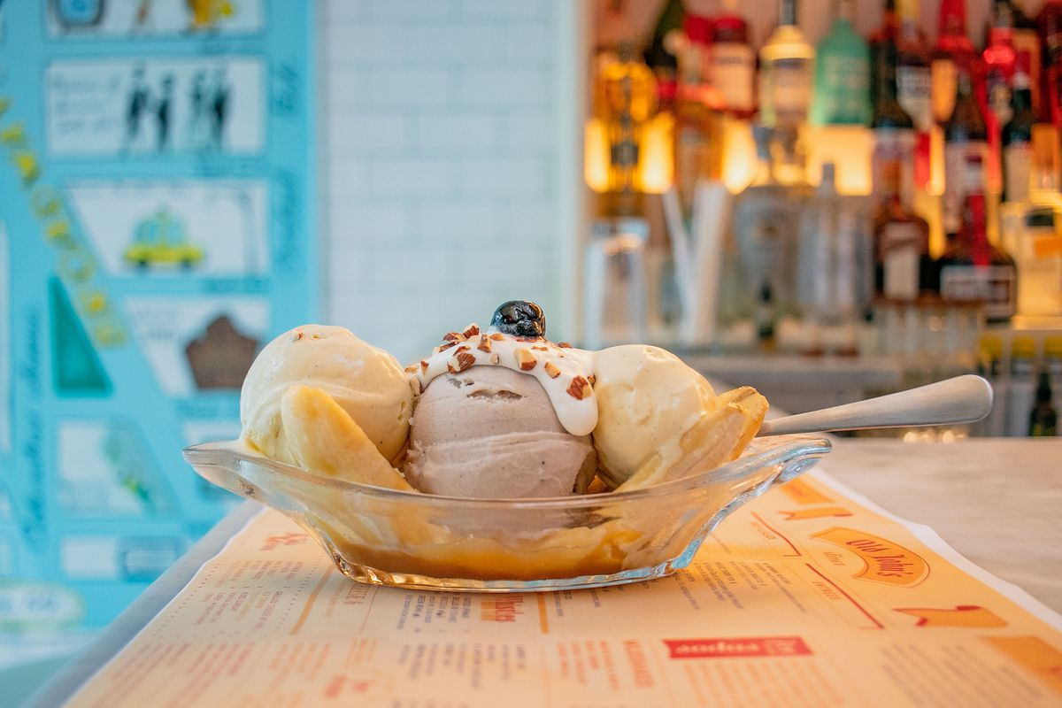 A clear glass dish filled with slices of banana and three scoops of ice cream with toppings set on a bar