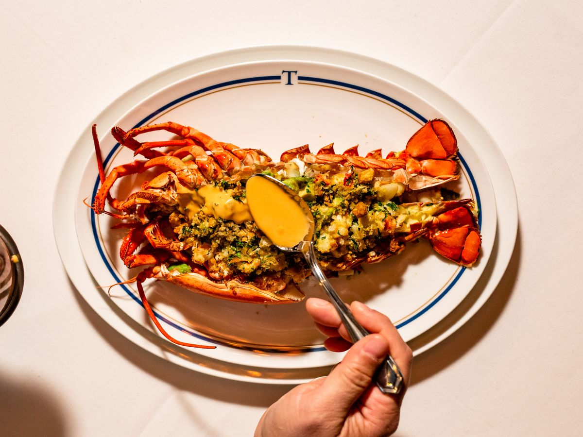 a whole lobster served thermidor-style, with a handle holding a spoon drizzling sauce over it
