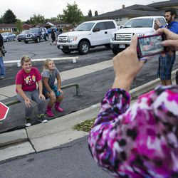 Noah Worton, 10, and his sister, Navie, 8, pose for a picture while sitting on a stop sign that was flattened by a tornado that struck Washington Terrace on Thursday, Sept. 22, 2016. Officials said nobody was injured in the twister.