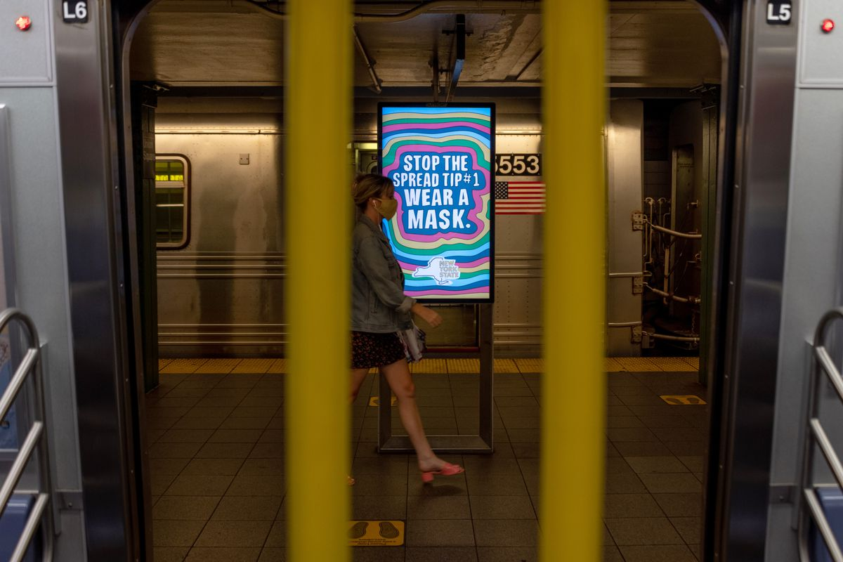 A woman wearing a mask walks past a wear a mask sign on a subway platform on June 25, 2020, in New York City.