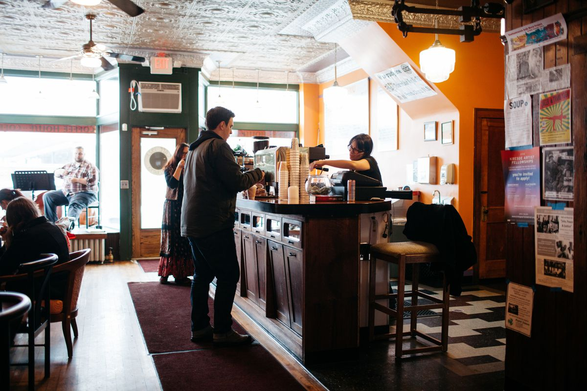 A man in a jacket and jeans stands at a shoulder-high coffee bar in a shop with orange walls and tin ceilings.