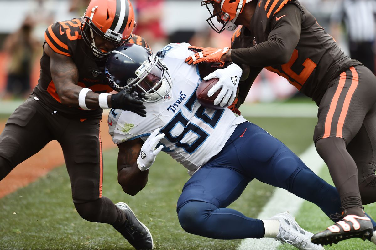 Tennessee Titans tight end Delanie Walker scores a touchdown as Cleveland Browns strong safety Damarious Randall and strong safety Morgan Burnett defend during the second half at FirstEnergy Stadium.