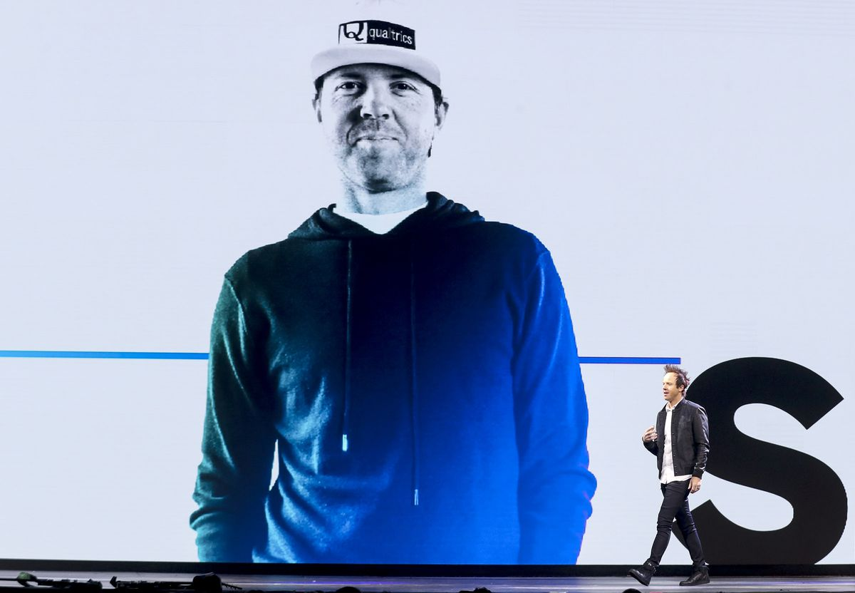 Ryan Smith, Qualtrics CEO, walks across the stage speaking during the Qualtrics X4 Summit at the Salt Palace Convention Center.