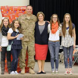 Air Force Tech Sgt. Edward Goettig poses with his family after returning home from active duty and surprising his four daughters individually at Fox Hollow Elementary in Lehi following his early return home on Thursday, March 6, 2014. Goettig had been deployed to Afghanistan since Aug. 27, 2013.