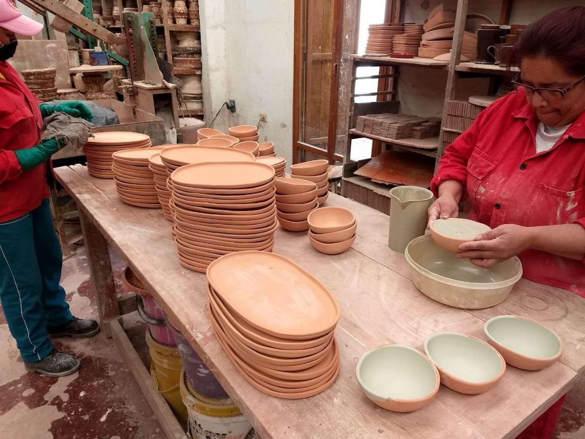 Two women standing at a work table with ceramic plates making ceramic plates