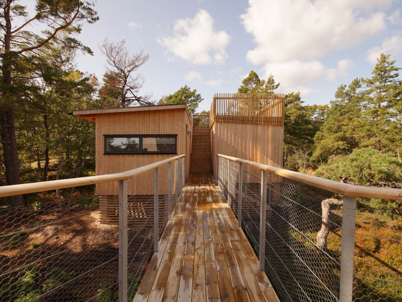Small wooden house on deck that's connected to a walkway.