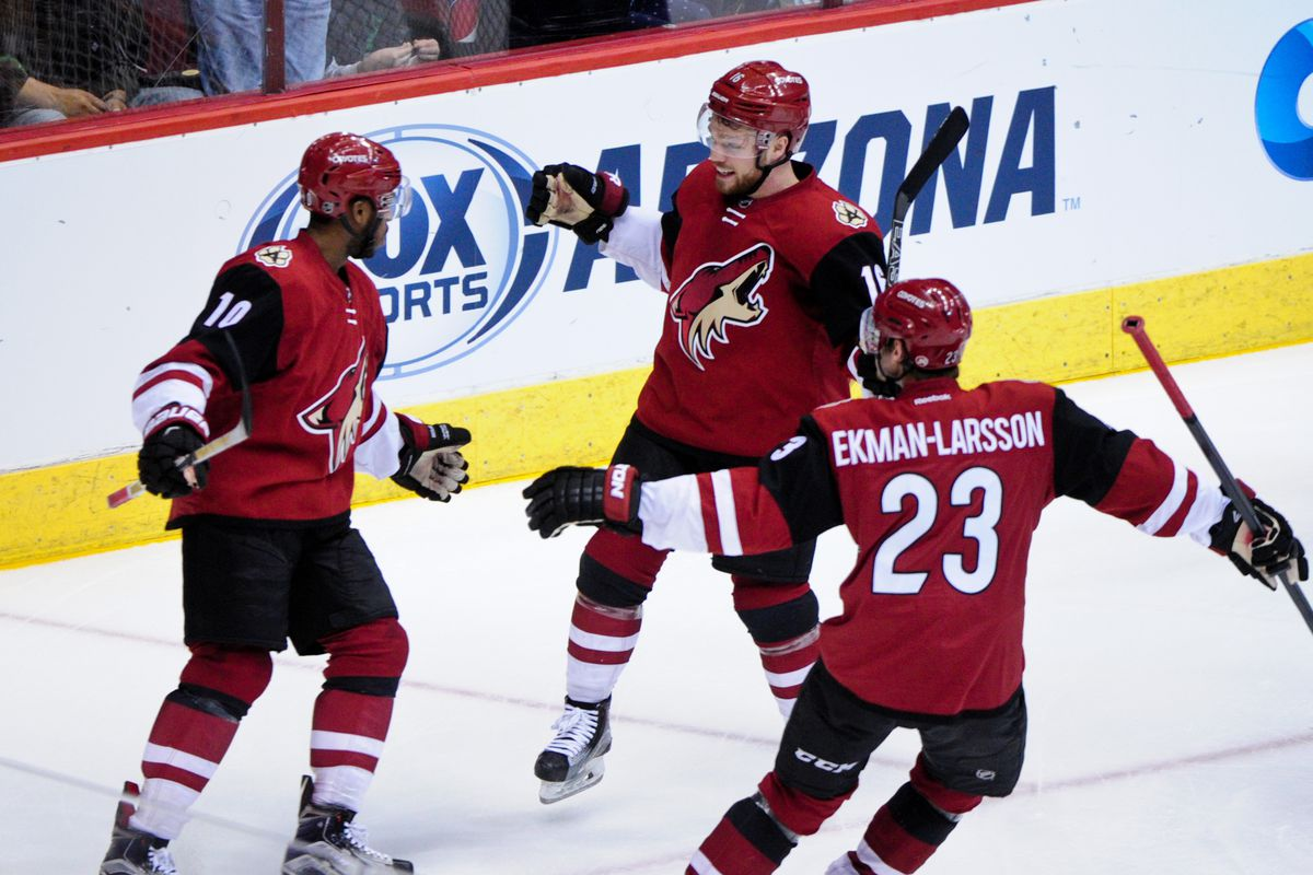 Feb 12, 2016; Glendale, AZ, USA; Arizona Coyotes left wing Anthony Duclair (10) celebrates with center Max Domi (16) and defenseman Oliver Ekman-Larsson (23) after scoring a goal in the second period against the Calgary Flames at Gila River Arena. Ma
