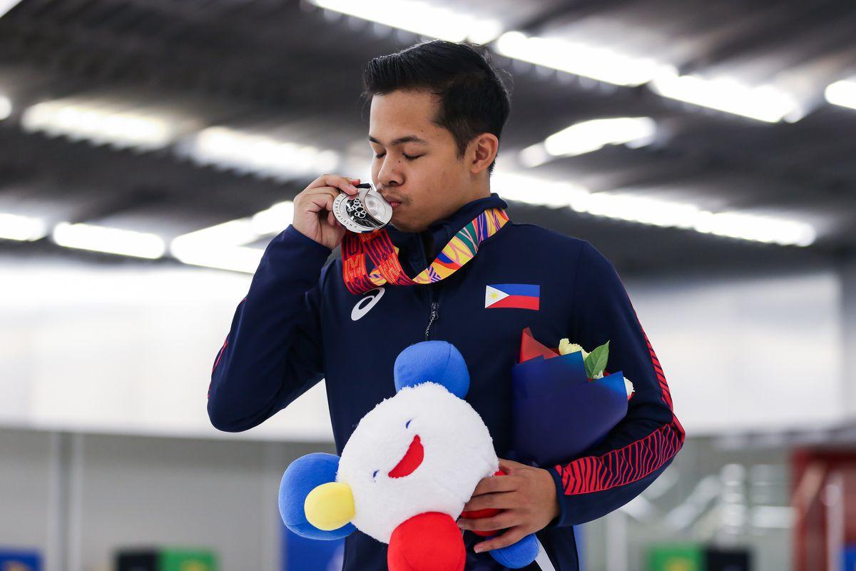 Christopher Caluza kissing a medal.
