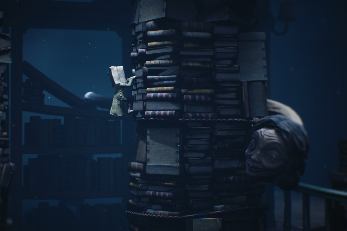 The school teacher monster from Little Nightmares 2 looks around a stack of books to find Mono