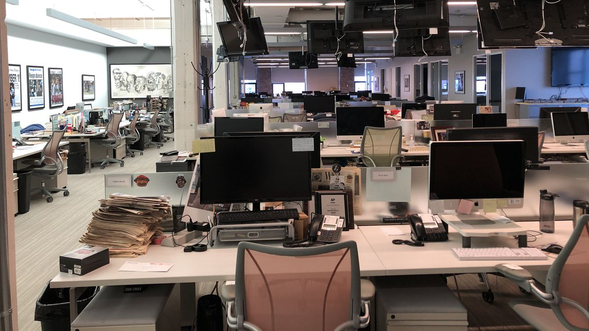 An empty newsroom with TV monitors hanging from the ceiling.
