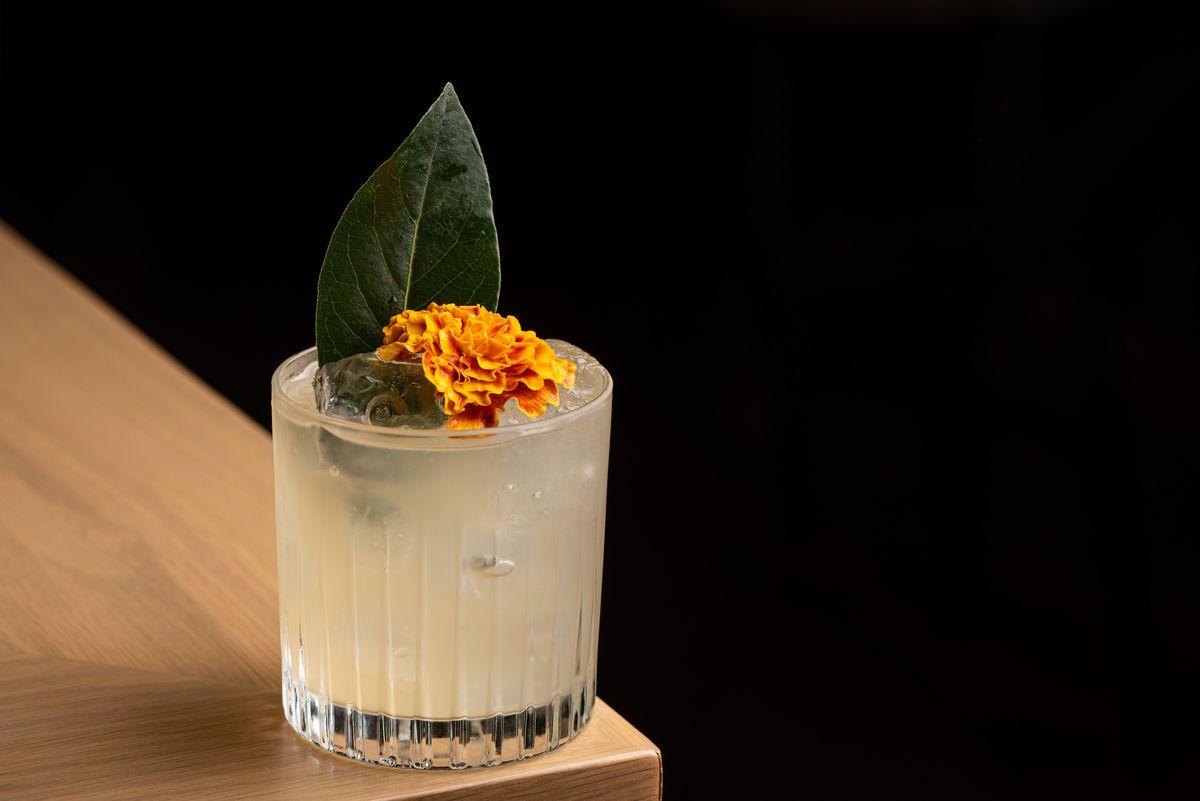 An off-white cocktail with marigold on top.