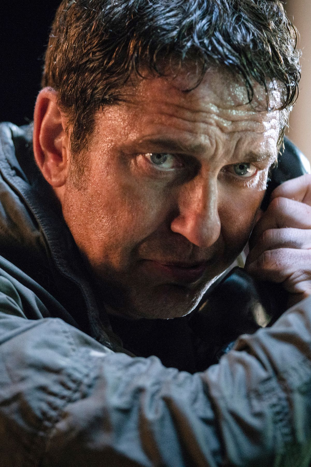 Mike Banning (Gerard Butler) acting paranoid and surly while talking on a pay phone — yes, really! — in Angel Has Fallen