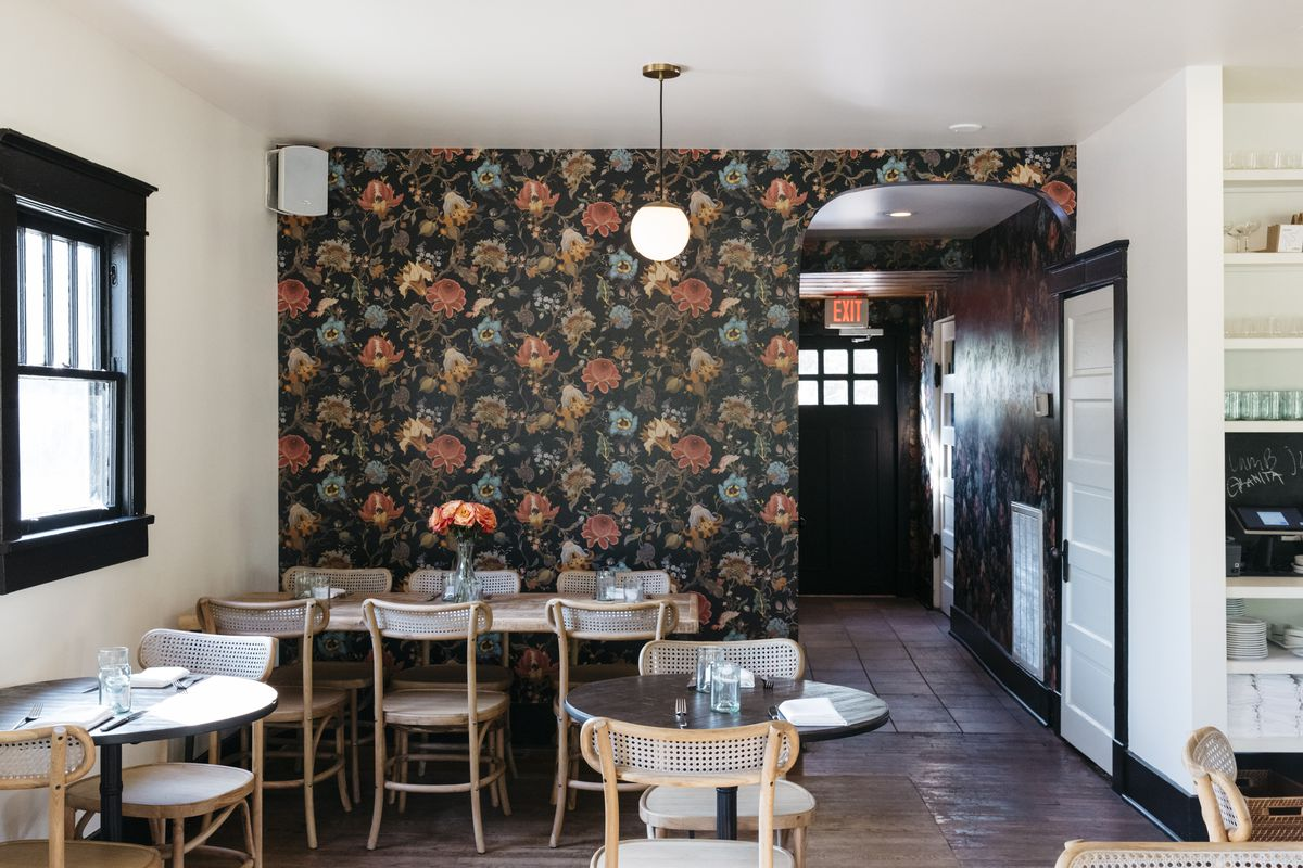 floral wallpaper covers a back wall, an orb light hangs from the ceiling, a few wooden chairs and tables are scattered throughout