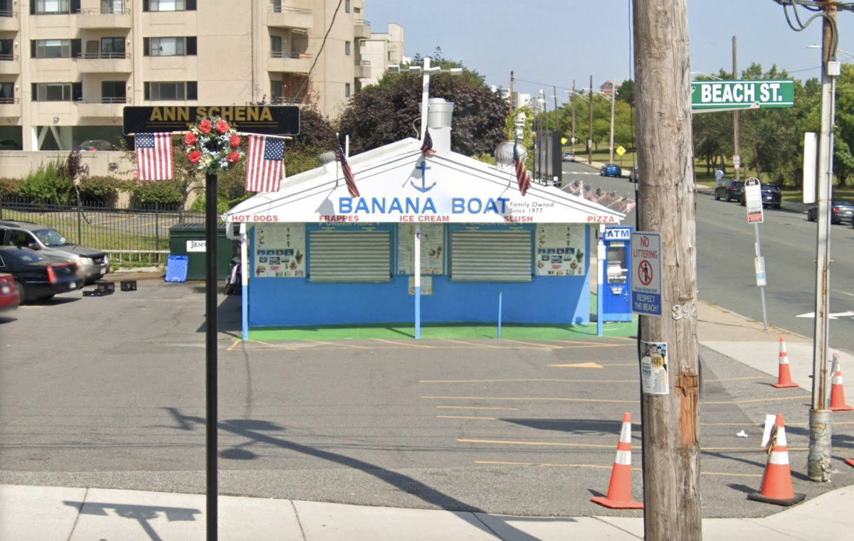 A shuttered ice cream shop, painted white and blue, with parking cones scattered in the parking lot and American flags hung from the facade