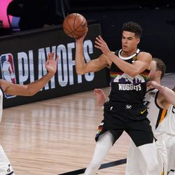 Denver Nuggets' Michael Porter Jr. (1) makes a pass as Utah Jazz's Rudy Gobert (27), Joe Ingles center rear, and Royce O'Neale (23) defend during the second half an NBA first round playoff basketball game, Tuesday, Sept. 1, 2020, in Lake Buena Vista, Fla.
