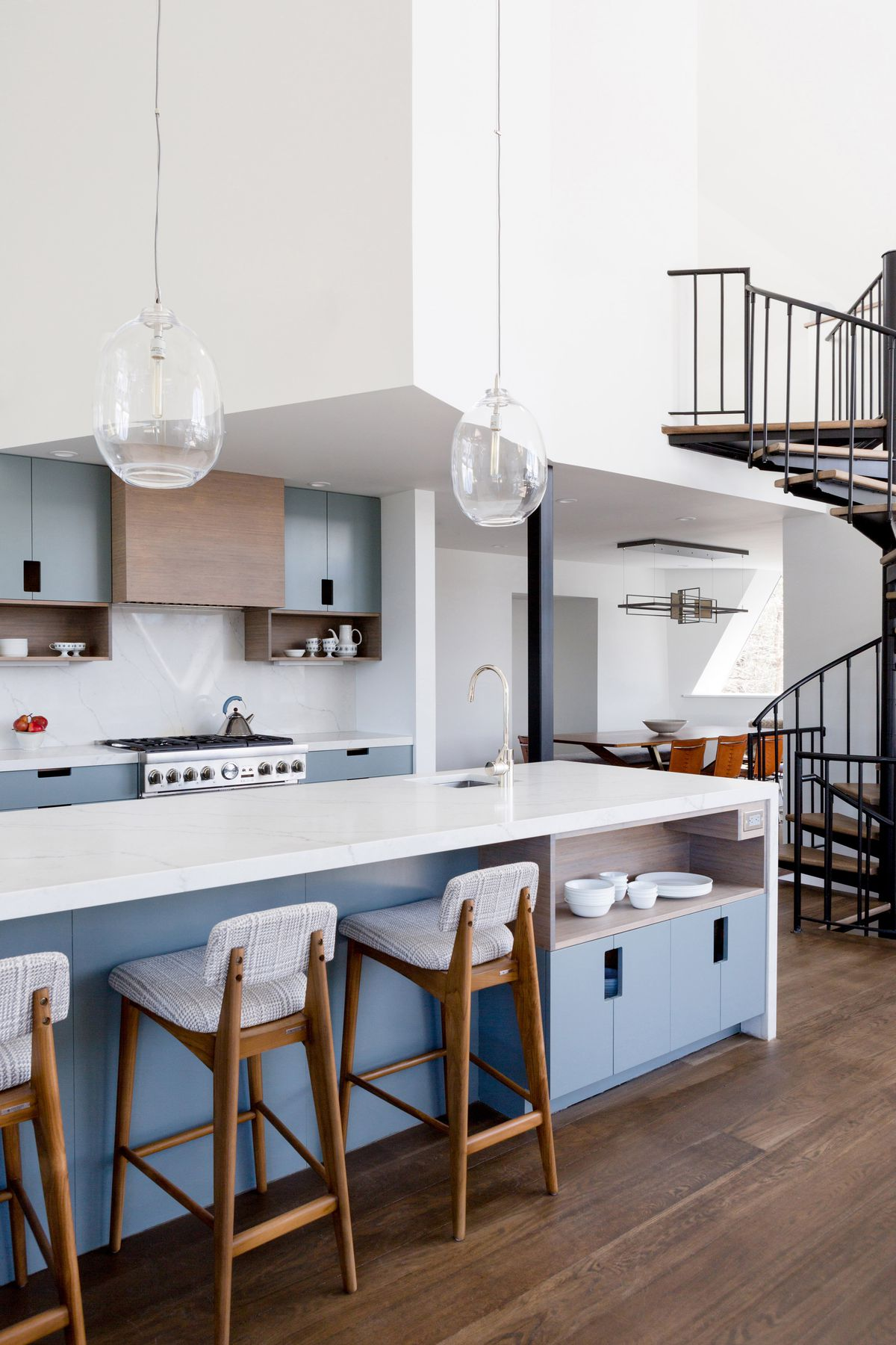 A modern kitchen with white counters and blue cabinets  is under high ceilings and next to a metal spiral staircase.