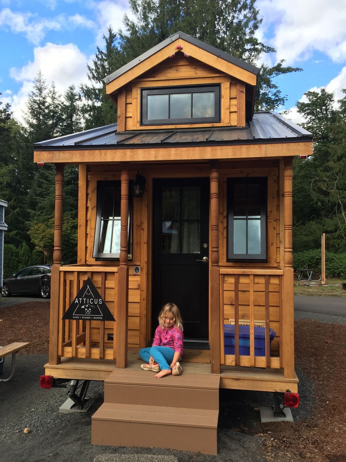A young girl sits on the porch of a tiny home called Atticus.