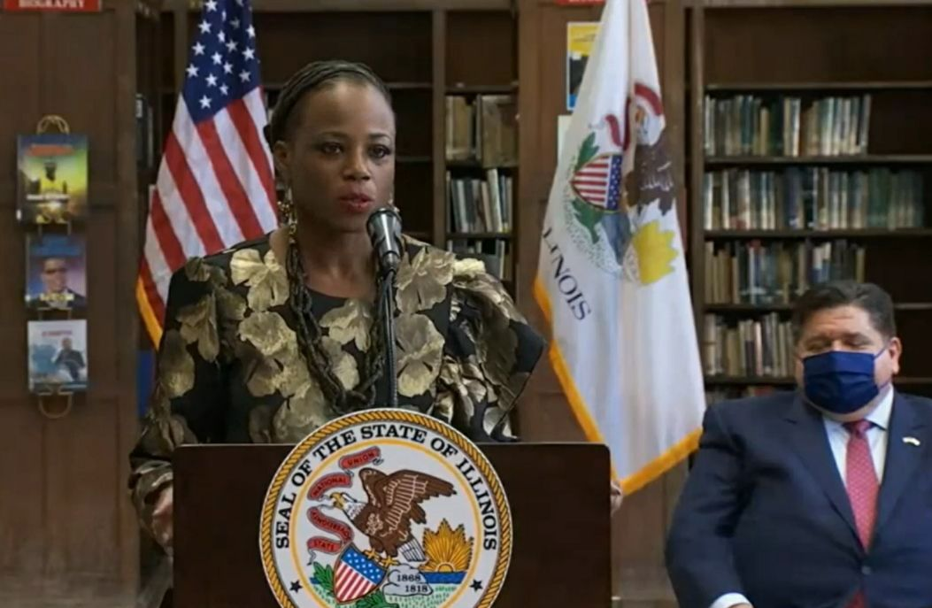 State Rep. Carol Ammons, D-Urbana, speaks at a bill-signing ceremony last month, shortly before Gov. J.B. Pritzker, right, signed the bill.