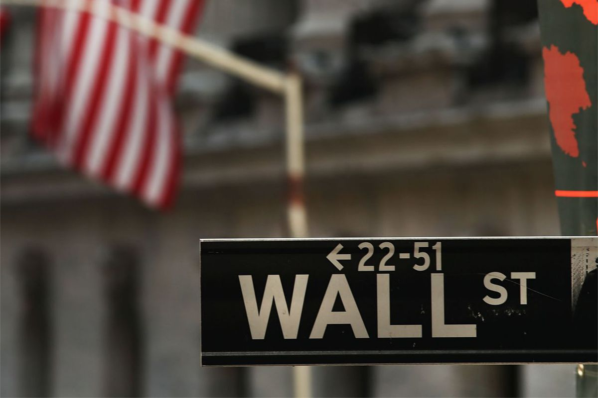 """A street sign that reads """"Wall St"""" with a building and an American flag in the background"""